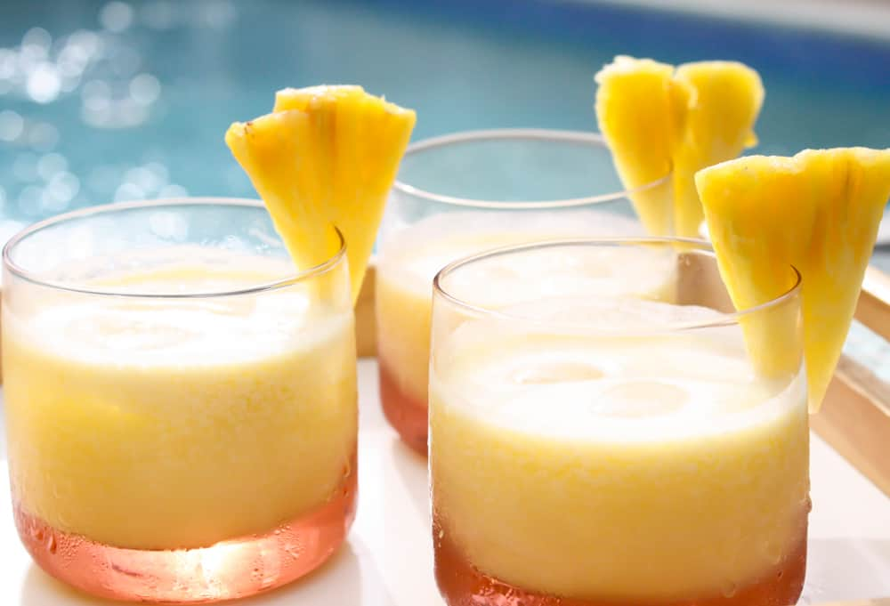 Pineapple coconut rum cocktail by a pool.