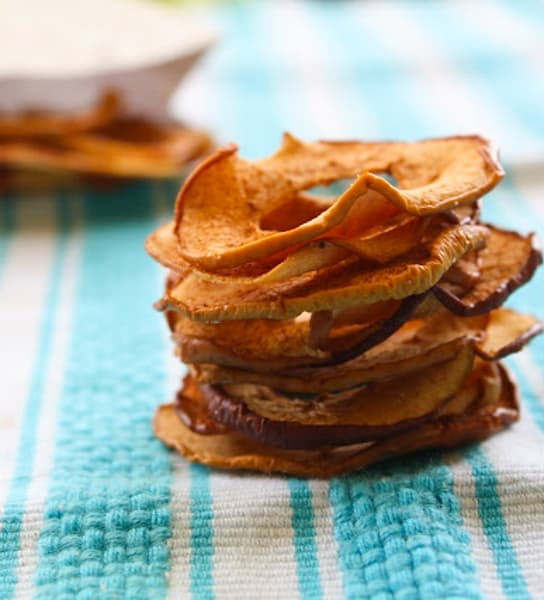 Stack of apple cinnamon chips on a bleu table cloth.