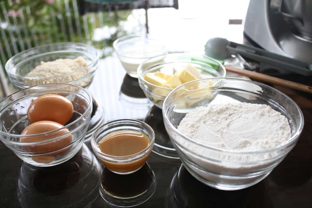 Wet and dry baking ingredients in bowls, on a table.