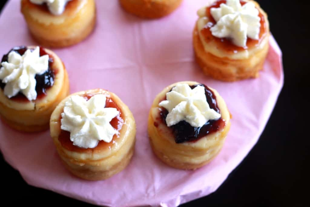 Overhead shot of mini cheesecakes on a cake stand.