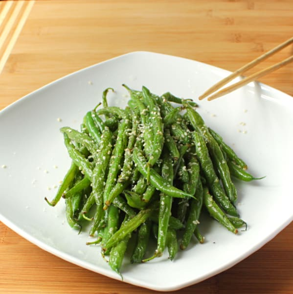 Green beans in a white dish with chopsticks.