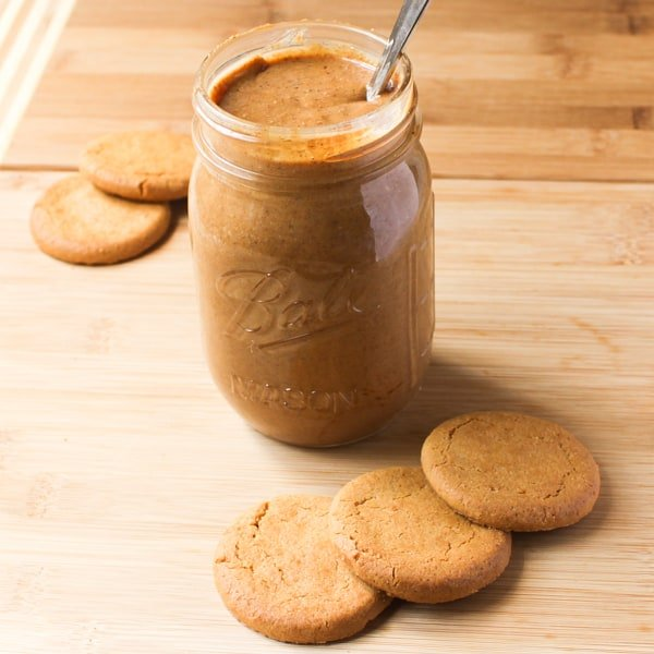 Cookie butter in a glass with cookies around it.