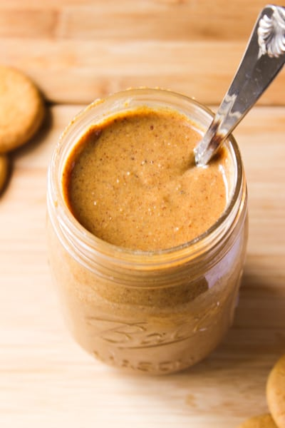 Overhead shot of cookie butter in a glass jar with a spoon.