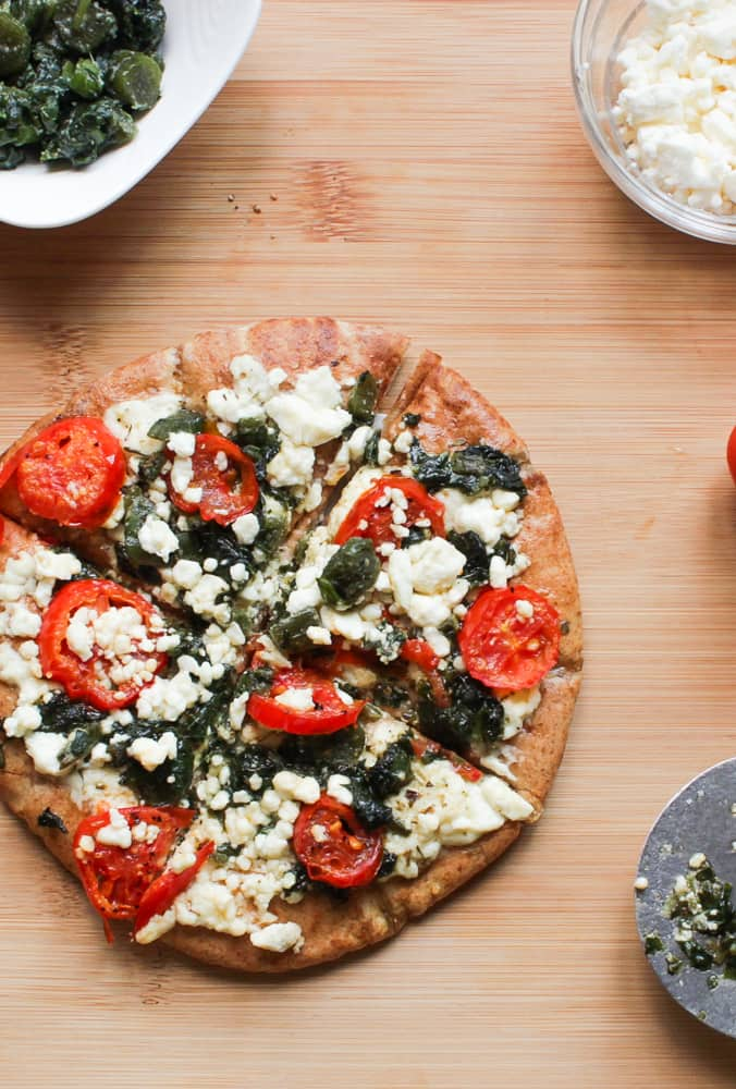 Callaloo, Feta and Roasted Tomatoes Pizza on a wooden table with ingredients.