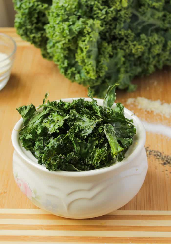 Crispy kale chips in a white bowl.