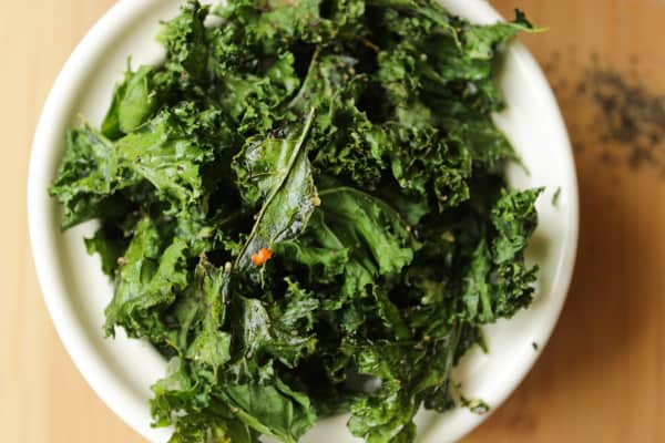 Overhead shot of crispy kale in a white bowl.