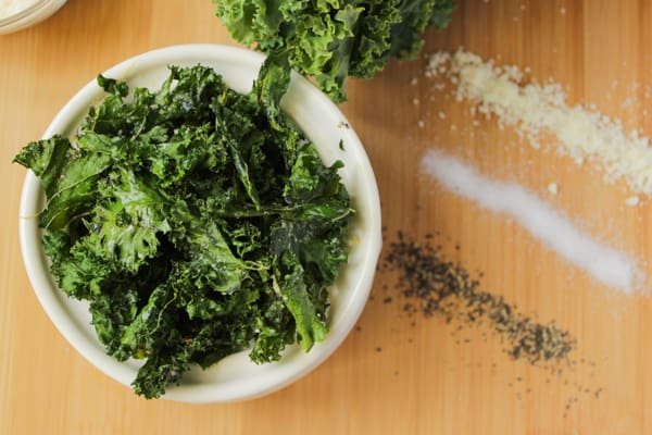 Kale chips in a bowl with seasoning on the side.