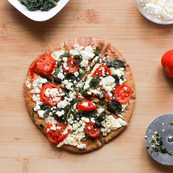 Top down shot of callaloo, feta and roasted tomatoes pizza.