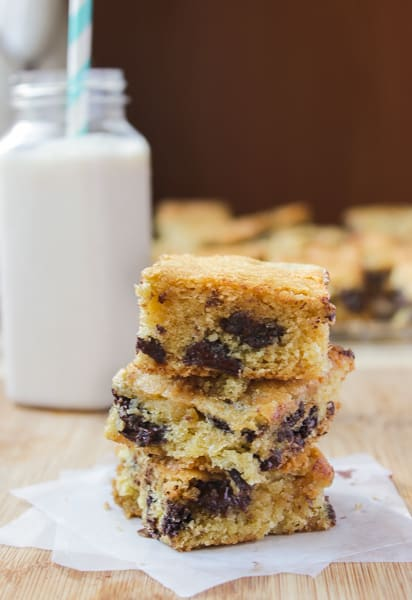 Stack of Chocolate Chip Cookie Bars with a glass of milk in the background.