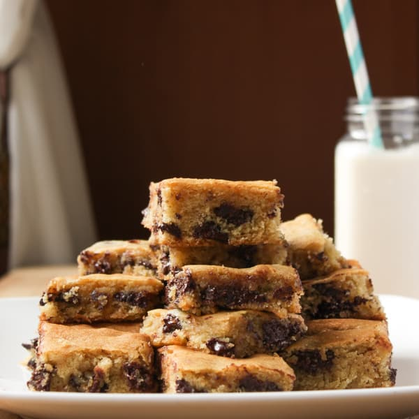 A pile of Ghirardelli Chocolate Chip Cookie Bars on a white plate.
