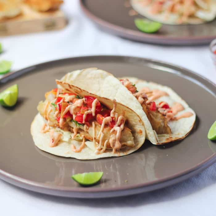 Beer battered fish tacos with sriracha mayo on a grey plate.