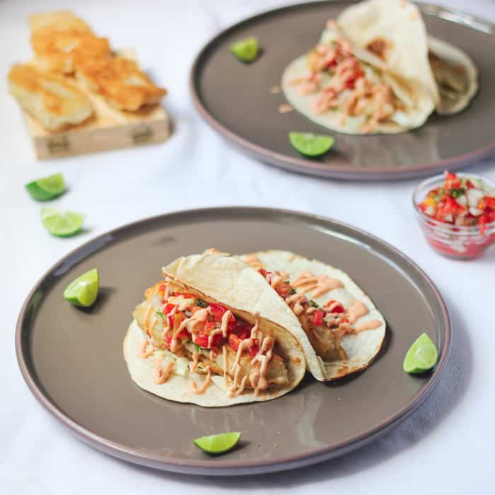 Fish Tacos on two grey plates with lime wedges.