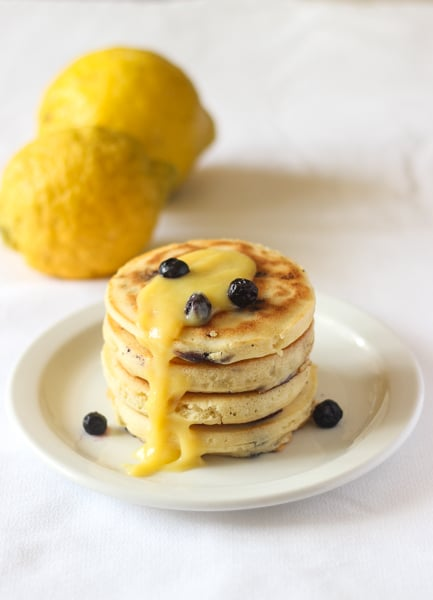 Stack of blueberry lemon pancakes with lemon curd on a white plate.