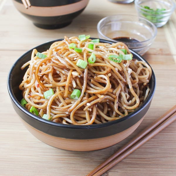 Sesame Noodles with Honey Ginger Sauce in a black and brown bowl with chopsticks are on the side.