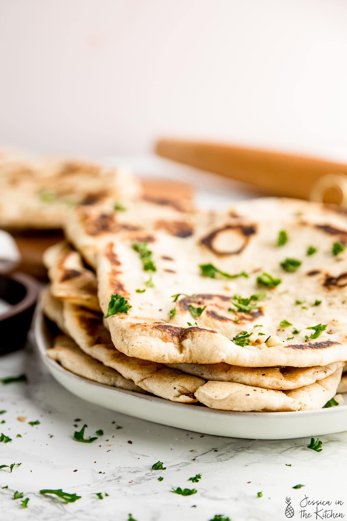 A head-on shot of vegan naan bread stacked on each other.