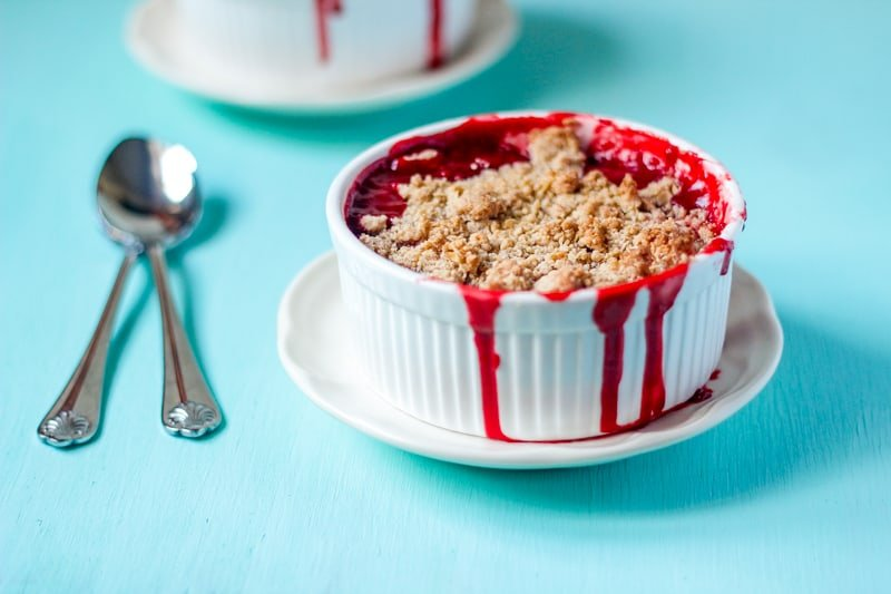 Side on shot of strawberry crumble in a ramekin on a blue table.
