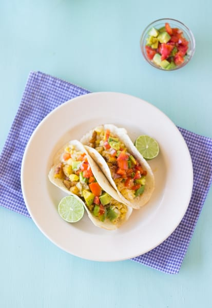 Breakfast tacos on a white plate.