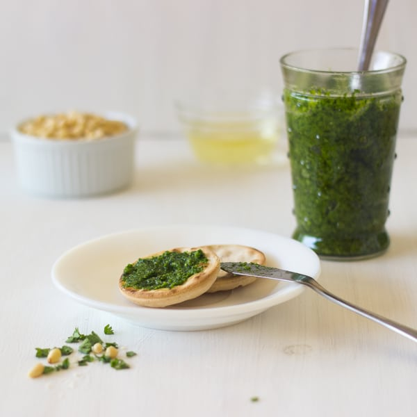 Parsley pesto on crackers with a jar of pesto in the background.