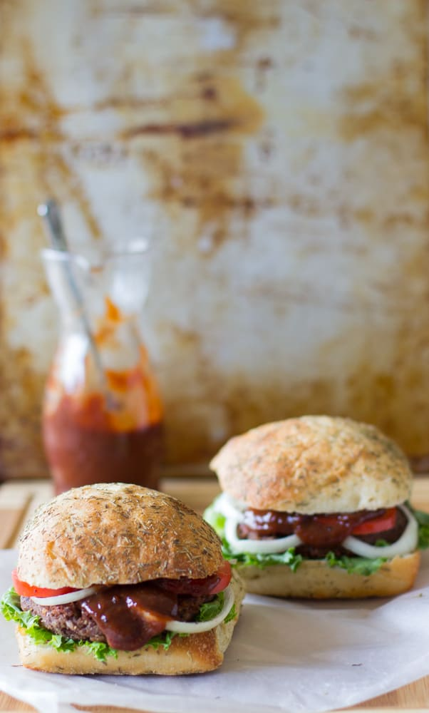 Side shot of two black bean and quinoa burgers on parchment paper.