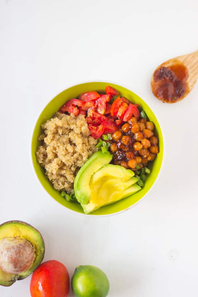 Honey & lime quinoa salad bowl with spicy BBQ chickpeas in a green bowl.