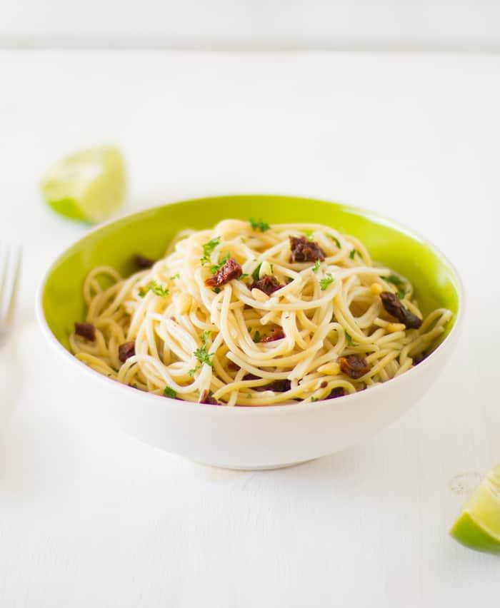 Side shot of lemon garlic spaghetti in a green bowl.