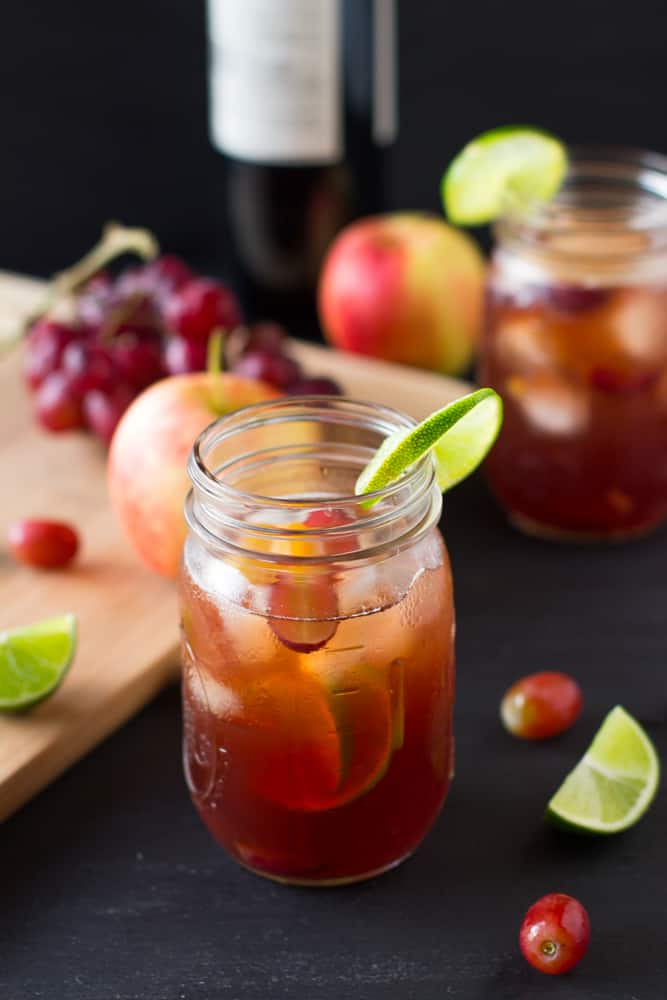 Rose sangria in a mason jar on a black table.