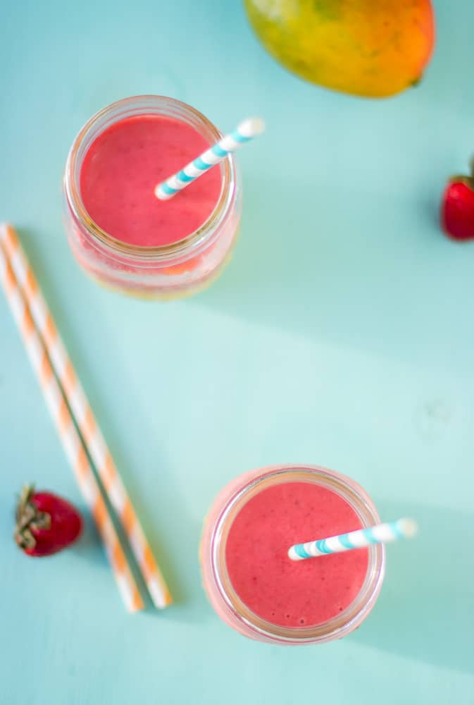 Top down shot of strawberry mango smoothies with straws.