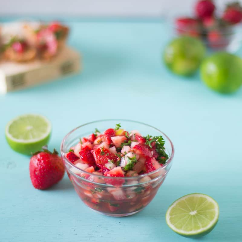 Bowl of  salsa with lime on the side.