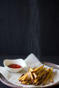 Salt falling on sweet potato fries
