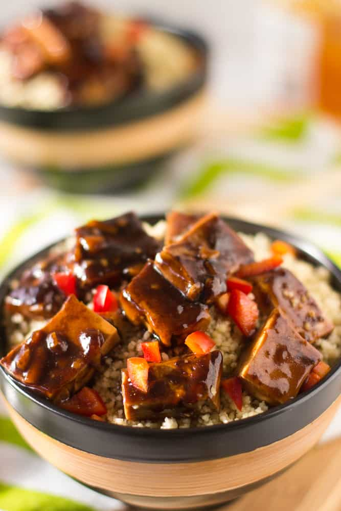Orange glazed tofu in a brown and black bowl.