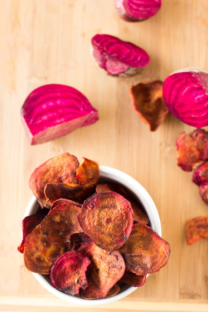 Top down shot of beet chips in a ramekin on a wooden table.