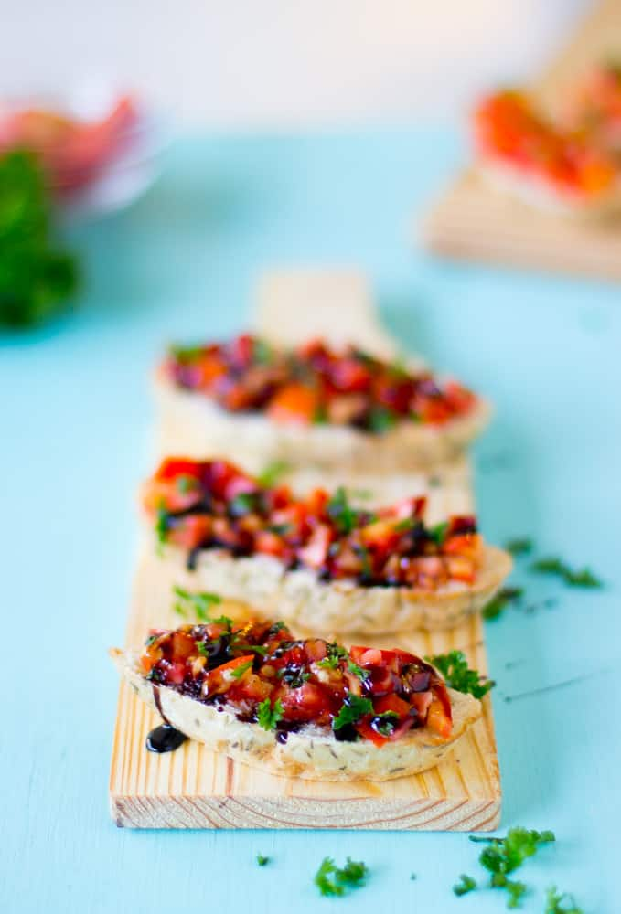 Bruschetta's on a wooden board drizzled with balsamic.