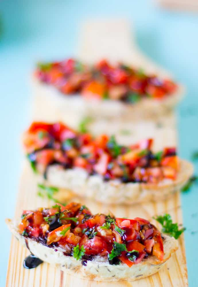 A row of three bruschetta on a wooden board.
