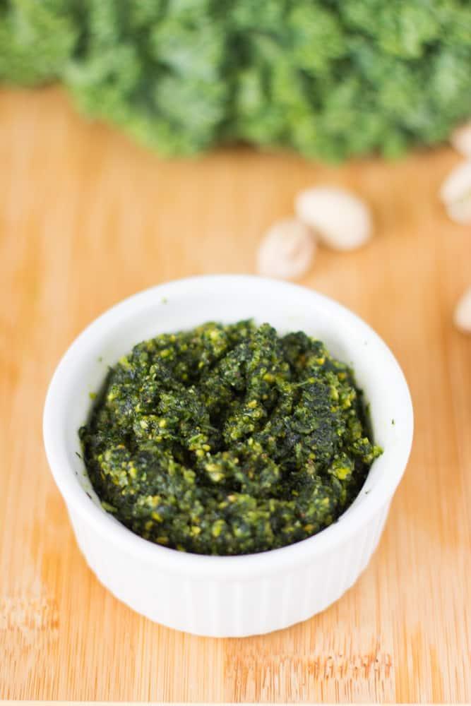Kale pistachio pesto in a white ramekin on a wooden board.