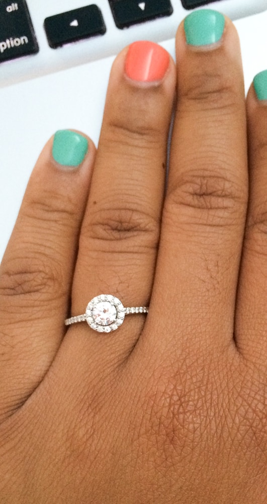 Top down shot of engagement ring on hand.