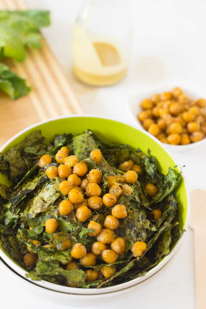 Close up of chickpea salad in a green bowl.