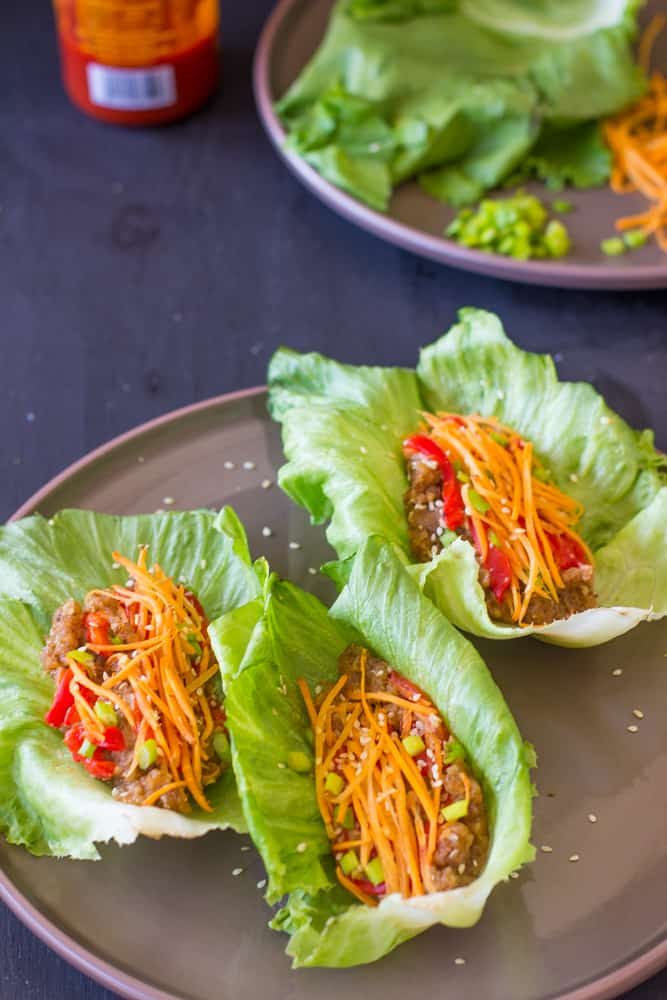 Three lettuce wraps on a grey plate.