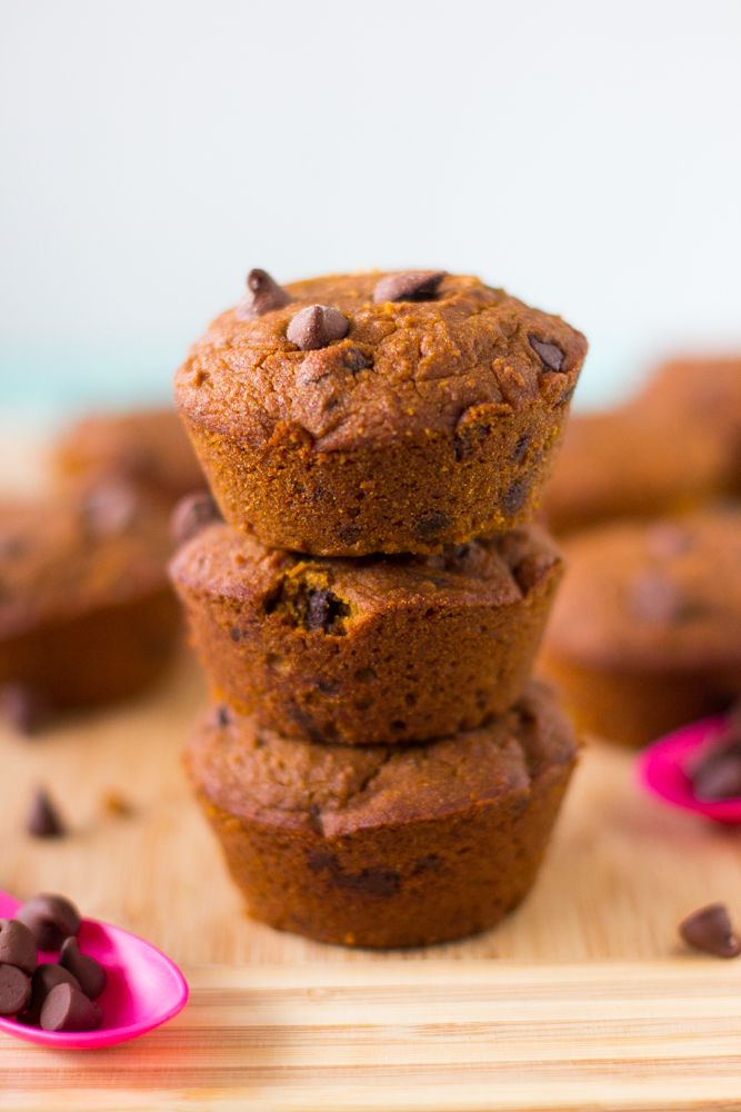 A stack of three pumpkin muffins on wooden table top.