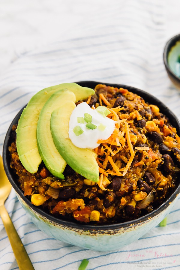 Vegan chili in a blue bowl with sour cream and slices of avocado on top.