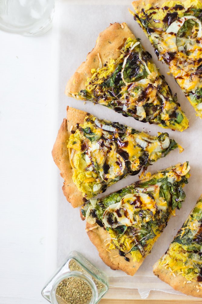 Slices of sweet potato and kale pizza on a white table.
