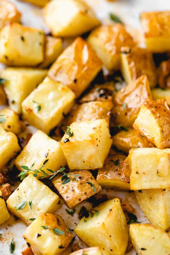 roasted potatoes on a baking sheet with thyme on top