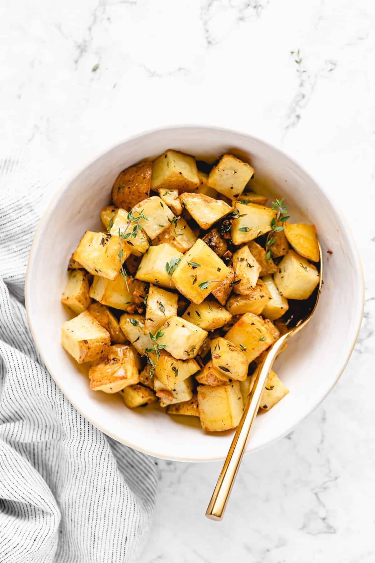 cooked garlic roasted potatoes in a large bowl with spoon in it