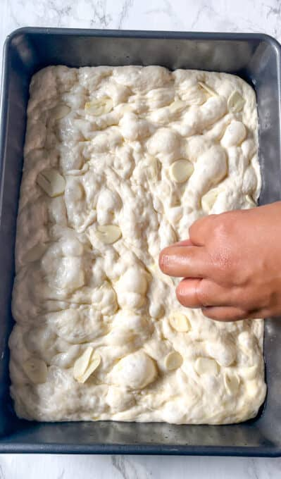 placing garlic slices onto focaccia dough