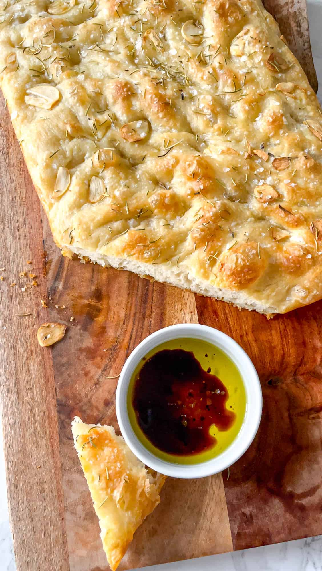 focaccia bread on a cutting board cut with a small bowl of balsamic vinegar and olive oil beside it