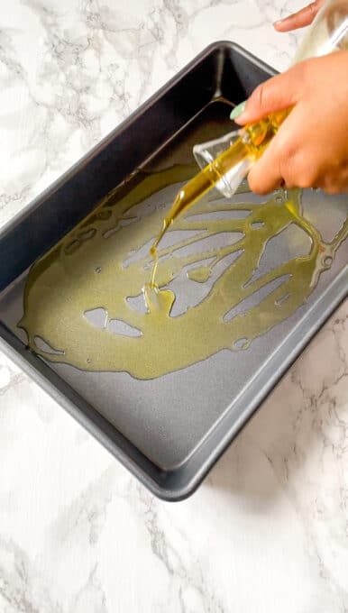 drizzling olive oil from a glass container into a baking dish