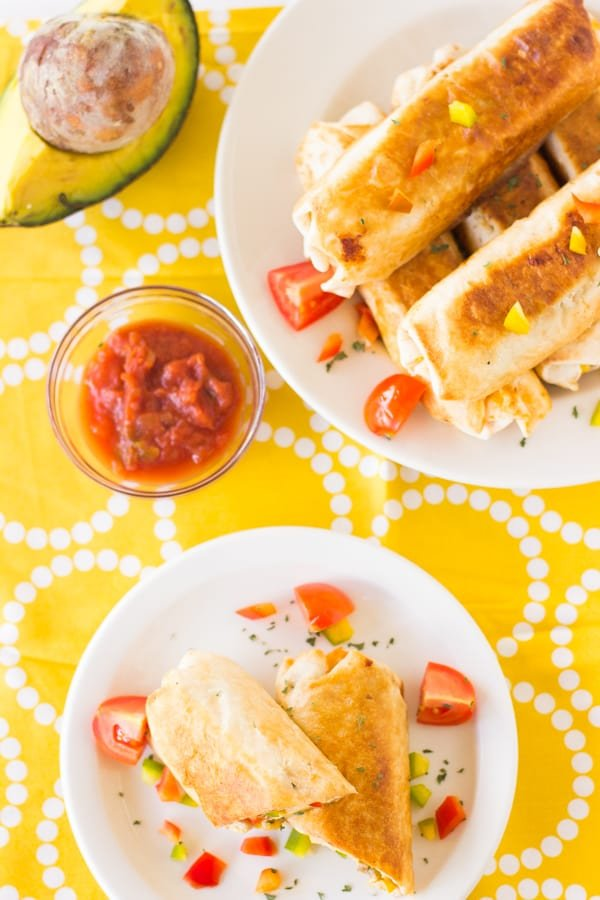 Top down shot of mexican breakfast burritos on a white plate.