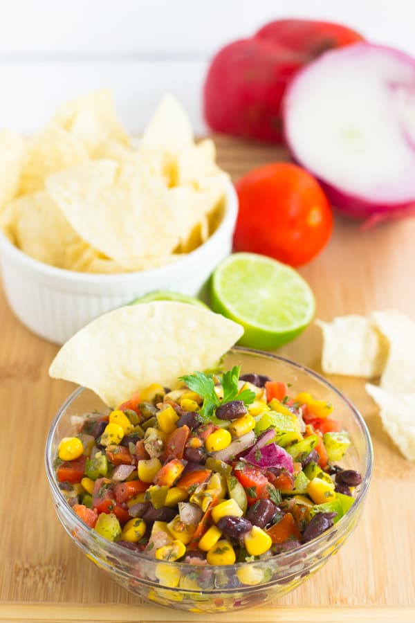Black Bean Salsa in a glass bowl with a chip in it.