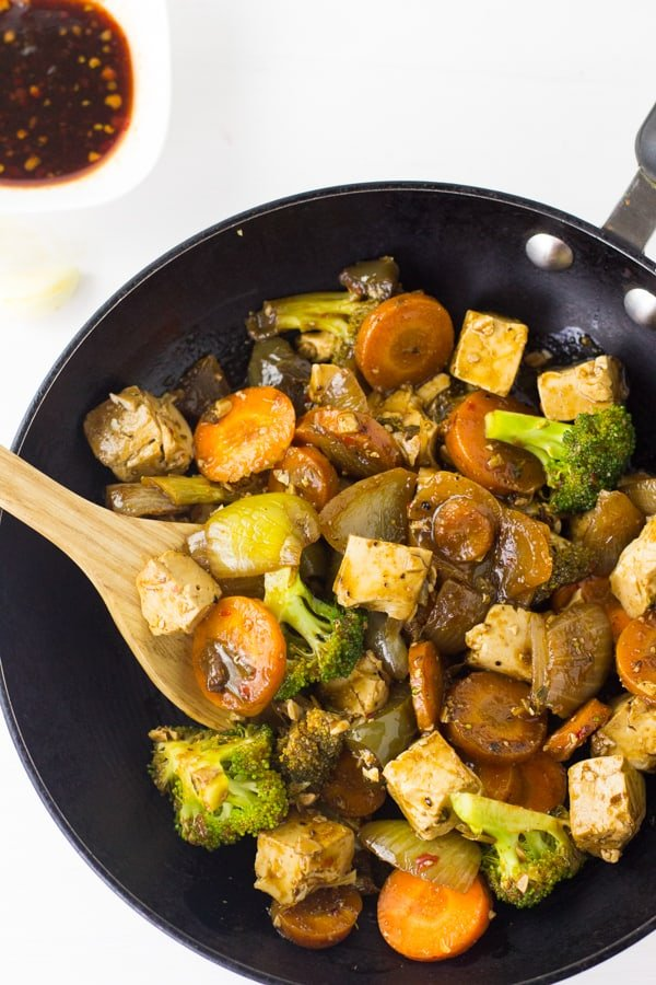 Overhead shot of tofu stir-fry in a black pan.