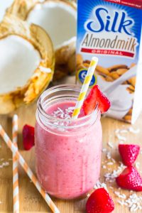 Strawberry coconut smoothie in a mason jar wit a straw and strawberries.