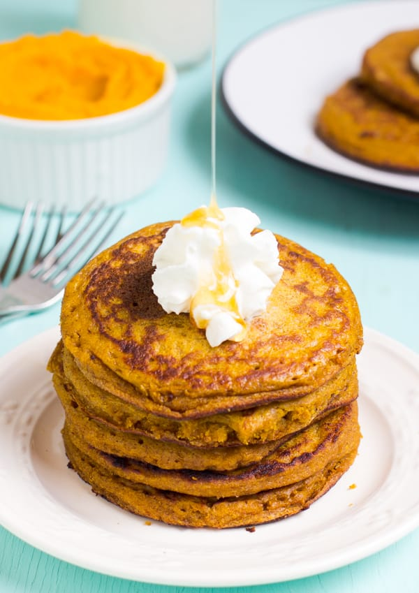A stack of gluten free pumpkin pancakes on a white plate.